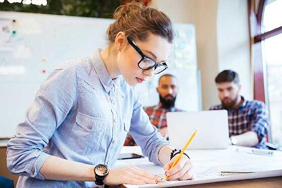 Woman engineer working on blueprint in office with colleagues on background